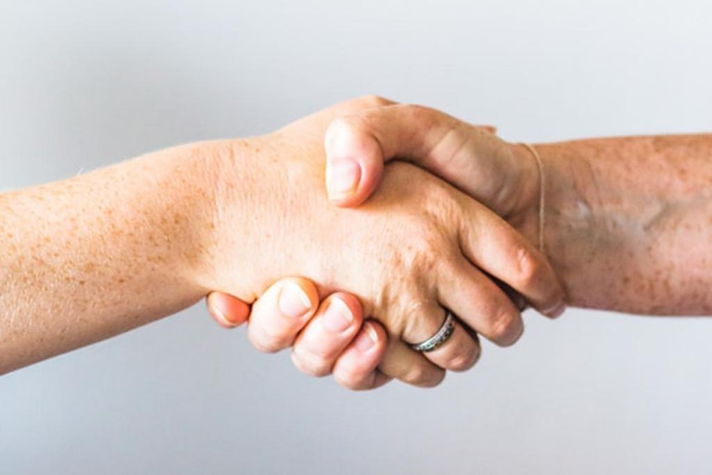 Billedet viser to personer der giver hånd.